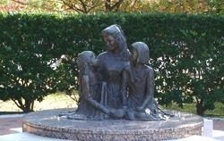 Stone monument of a woman and 2 children.